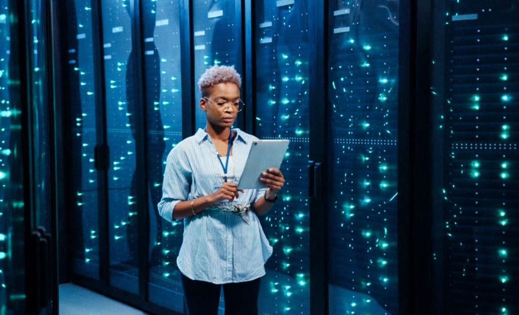 female excalibur IT administrator walking in server corridor diagnosing hardware system performance in data center cyber secure storage.