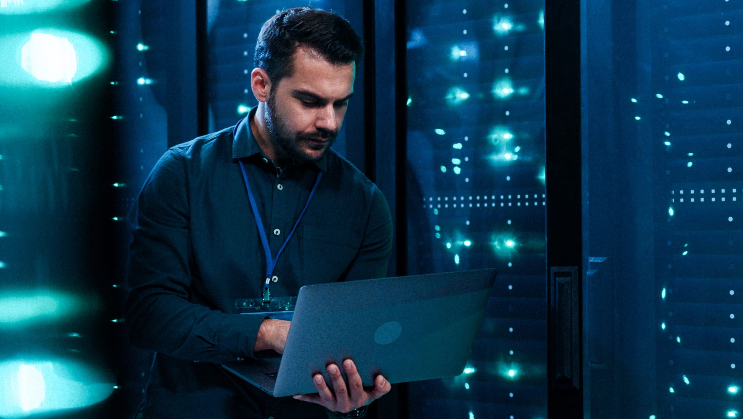IT professional admin using laptop computer doing data transfer operation with rack server cabinets in digital room of data center. Cyber security.