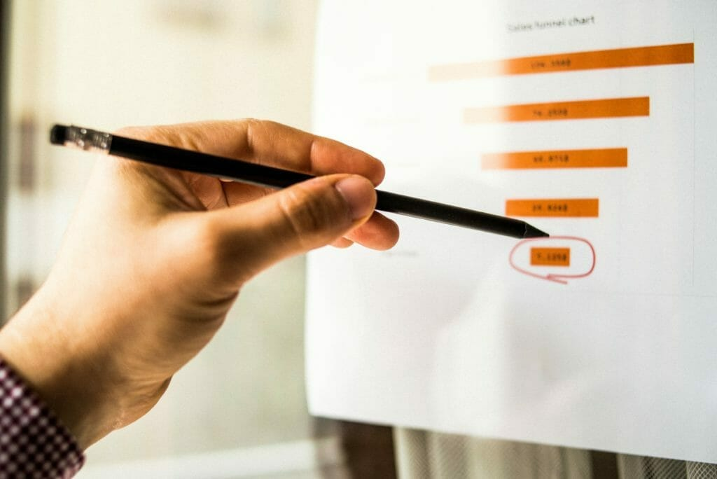 Male hand pointing with a finger at a sales funnel chart printed on a sheet of paper during a ExCALIBUR Funding meeting
