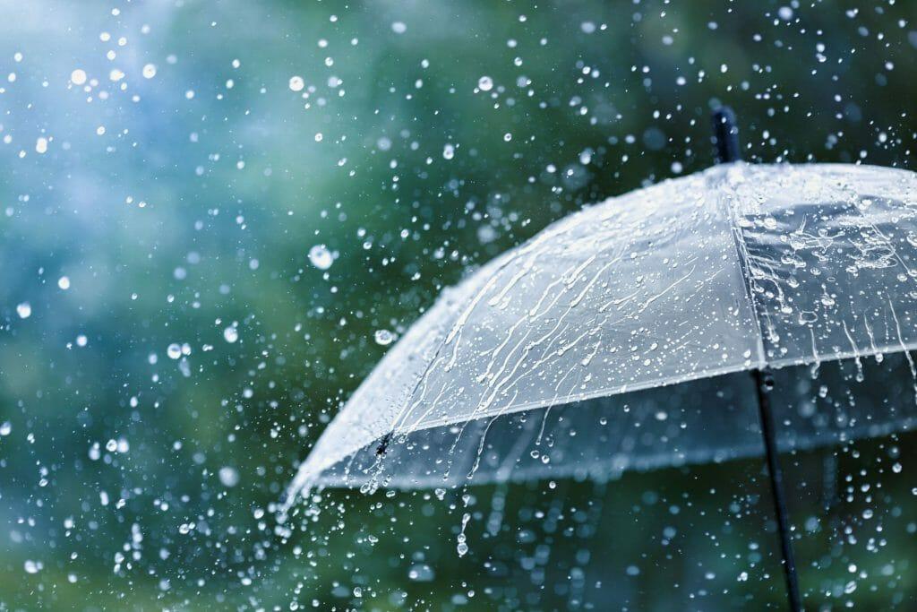 Transparent umbrella under rain against water drops splash background.